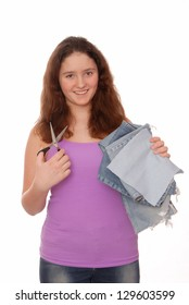 Creative teenager holds scissors and pieces of jeans.