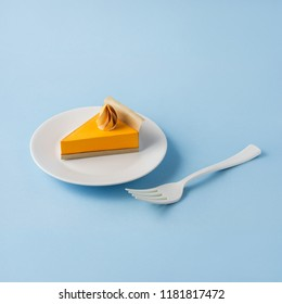 Creative thanksgiving day concept photo of a pumpkin pie made of paper on blue background.