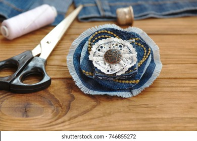 Creative things to do with old jeans. Handmade denim flower brooch. Scissors, thread, thimble, needle, female old jeans on a wooden background. What to do with torn jeans. Closeup
