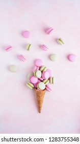 Creative top view of colorful macarons in a waffle cone with copy space on color background. Concept of cafe, bakery, dessert, girl's blog. Template for your text or design.