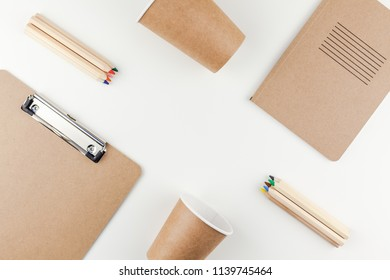 Creative top view flat lay of workspace desk styled recycled brown design office supplies and coffee cups with copy space white table background minimal eco style. Concept of environmental protection