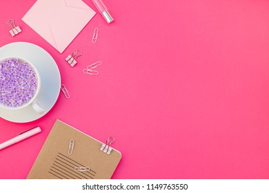 Creative top view flat lay of workspace desk styled design office supplies and cup of tea with copy space on a bright pink color paper background minimal style. Template for feminine blog social media