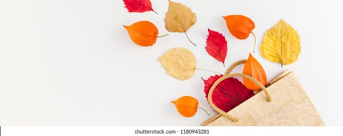 Creative Top view flat lay autumn composition Shopping bag dried orange flowers leaves background copy space Template sale mockup fall harvest thanksgiving halloween promotion flyers. Long wide banner