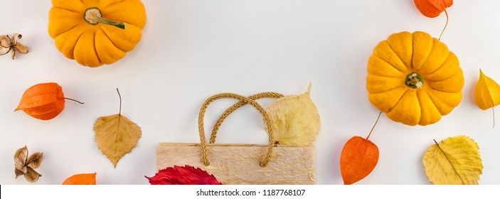 Creative Top view flat lay autumn composition Shopping bag dried orange flowers leaves pumpkins background copy space sale fall harvest thanksgiving halloween promotion flyers text Long wide banner