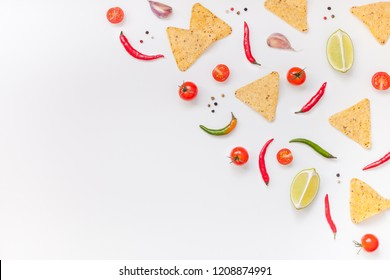 Creative Top view flat lay of fresh mexican food ingredients with tortilla nachos chips garlic pepper lime tomatoes on white table background with copy space. Food preparation cooking concept frame