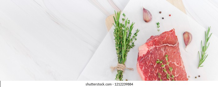 Creative Top view flat lay of fresh raw beef meat striploin steak with rosemary thyme herbs garlic pepper mushrooms on white marble table copy space. Food preparation cooking concept Long wide banner