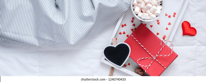 Creative Top view flat lay sill life romantic composition. Hot cacao coffee chocolate with marshmallows mug red gift hearts tray in bed Concept Valentine holiday morning natural light Long wide banner
