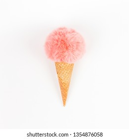 Creative top view flat lay of coral color fluffy fur ball in ice cream waffle cone with copy space on white background in minimal style. Concept feminine blog social media. Natural light with shadows