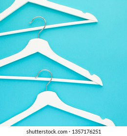 Creative top view flat lay white wooden hangers isolated bold blue turquoise background with copy space minimalism style. Template fashion feminine blog sale store promo design shopping concept