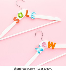 Creative top view flat lay white wooden hangers sale text pastel pink background copy space minimalism style. Template fashion feminine social media sale children store promo design shopping concept