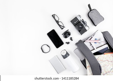 Creative top view flat lay of open backpack with laptop and tablet inside, mobile phone map copy space white background minimal style. Concept of modern man accessories for travel adventures and life