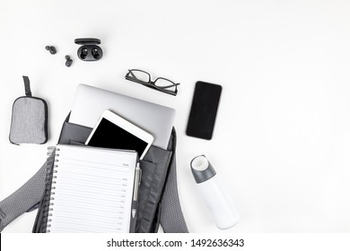 Creative top view flat lay of open backpack with laptop and tablet inside, mobile phone, copy space white background minimal style. Concept of modern man accessories for education, business and life