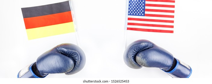 Creative top view flat lay of Two boxing gloves with Germany and USA flag and copy space on white background in minimal style. Concept of confrontation between USA and Germany