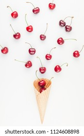 Creative top view of ripe cherries in a waffle cone with copy space isolated on white background in minimal style. Concept of summer fun and healthy eating. Template for your text or design.