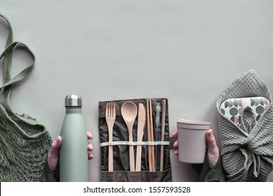 Creative top view, zero waste packed lunch concept, takeaway lunch box set with bamboo cutlery, reusable box, cotton bag and hand with coffee-to-go cup above on craft paper. Sustainable lifestyle.