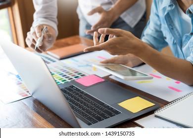 Creative UI designer teamwork meeting planning designing wireframe layout  application development mockup on smartphone screen for web mobile phone technology