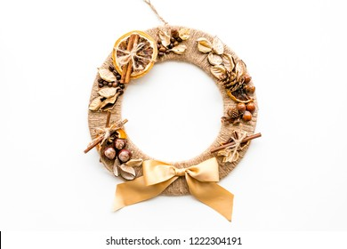 Creative, unusual christmas wreath made of thread, dry fruits and nuts on white background top view copy space