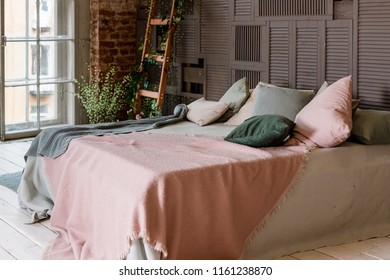 Creative use of small space in a stylish bedroom interior with designer decor and cozy white and beige bedding.Minimal loft style. Pastel soft colors.decorative ladder in interior