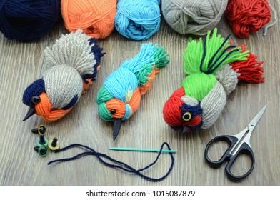 creative utensils to create yarn birds. Plastic eyes and scissors on table. yarn birds in style of kingfinsher, bullfinch and green woodpecker.