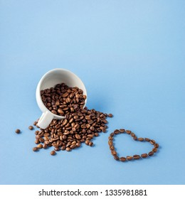 Creative valentine day concept photo of cup of coffee with love holiday celebration heart made of beans on blue background.