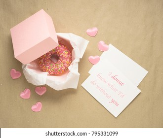 Creative valentine day concept photo of donut in box with hearts and notes with text on craft brown background.