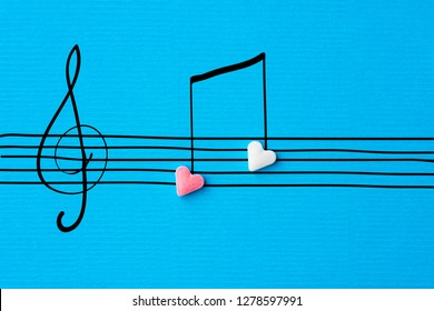 Creative Valentine greeting card. Sugar heart shape candies hand drawn doodle sketch musical notes on staff treble clef on linen texture blue paper background. Love song romantic concept