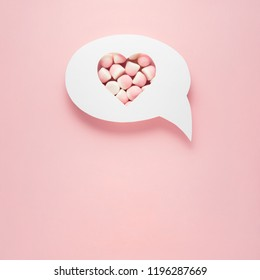 Creative valentines concept photo of comic cloud with heart and candies on pink background.