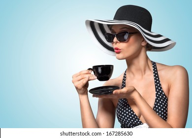 A creative vintage photo of a beautiful pin-up girl drinking tea and showing good table manners.