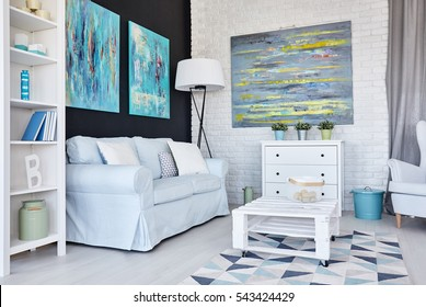 Creative white living room decorated with blue paintings