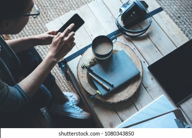 Creative woman artist with tablet pc, headphones and paperwork. Using mobile phone