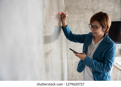 Creative woman in blue shirt drawing on the wall.