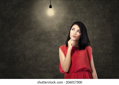 Creative woman looking at bright lightbulb