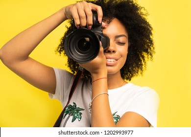 Creative woman-photographer takes photos, isolated on yellow