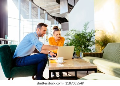 Creative worker showing project to client on laptop during meeting in cafe