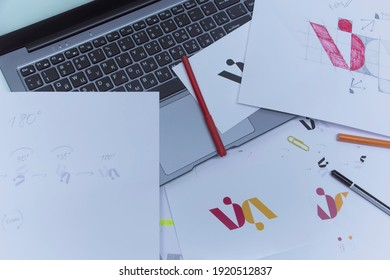 Creative workplace of a Graphic Designer. Development of a logo for the company. Drawings and sketches on paper in a art studio office