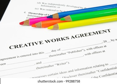 Creative Works Agreement with crayons in orange, pink, yellow, green and blue