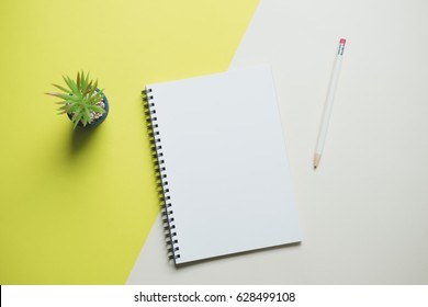 Creative workspace desk with notebook, and cactus on yellow background , minimal style