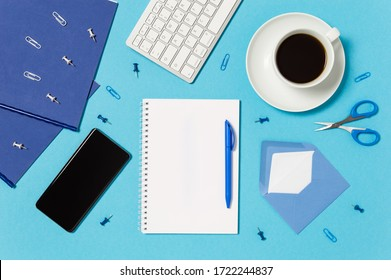 Creative workspace with keyboard, coffee cup, notepad, pen, mobile phone, envelope, scissors, pins and clips in blue and white. Home office concept. Blank paper with copy space. Flat lay, top view