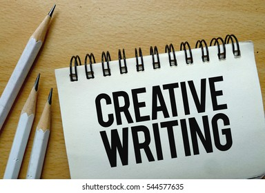 Creative Writing text written on a notebook with pencils