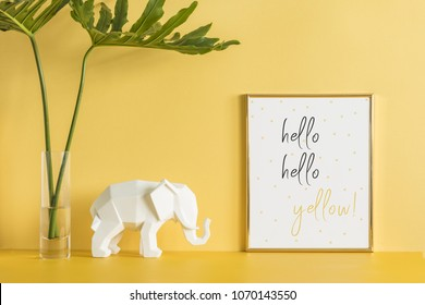 The creative yellow desk with leafs, elephant and poster frame. Modern office work space..