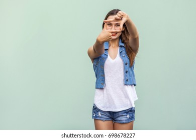 Creative young adult woman with freckles, making a frame gesture with her fingers as she looks through to visualise a project or the composition of a photograph. Indoor studio shot on green background