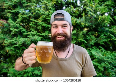 Creative young brewer. Craft beer is young, urban and fashionable. Distinct beer culture. Hipster brutal bearded man hold mug cold fresh beer. Man enjoying beer in summer. Alcohol and bar concept.