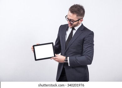 creative young engineer in a business suit with a tie and sunglasses presents with a smile on his face display a tablet.