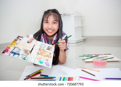 creative young girl kid holding stationary, ready for drawing and painting, little artist with smile pretty face, Asian tan skin model
