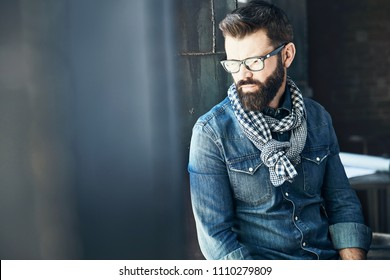 Creative young man with dark hair and beard, weared in denim jacket, scarf and eyeglasses is sitting near big window