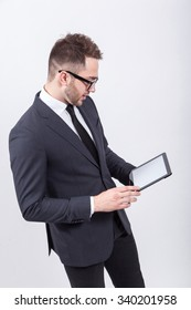 Creative young programmer in a business suit with a tie and sunglasses presents with a smile on his face display a tablet.