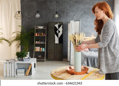 Creative young woman decorating her modern spacious room