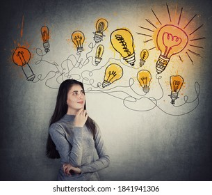 Creative young woman thinking of great ideas, looking at bright lightbulb sketches on the wall. Smart and ingenious student girl different thinking, genius solutions concept. Dream of alternative plan