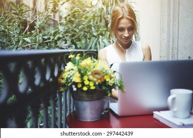 Creative young woman work on laptop during breakfast on her terrace, experienced female freelancer sitting at red balcony table front open computer, student girl working on a wireless net-book at home