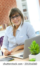 Creative young woman working in office with graphic tablet